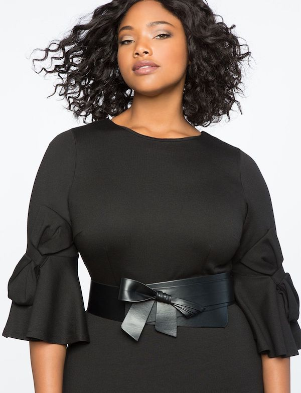 A plus-size model wearing a black wrap corset belt.