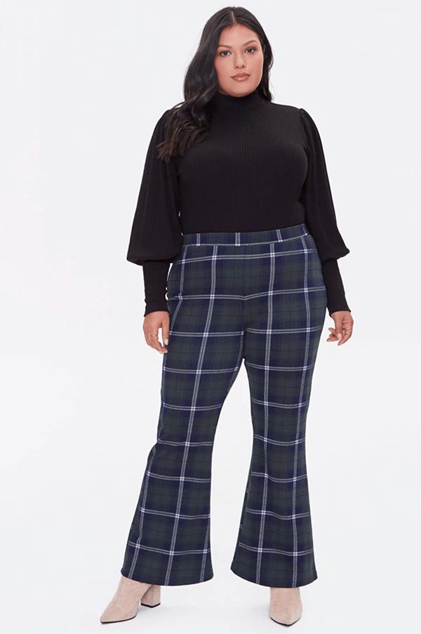 A plus-size model wearing a pair of navy plaid flare pants.