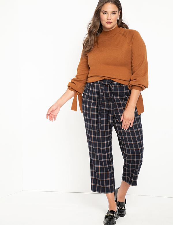 A plus-size model wearing a pair of black plaid pants.