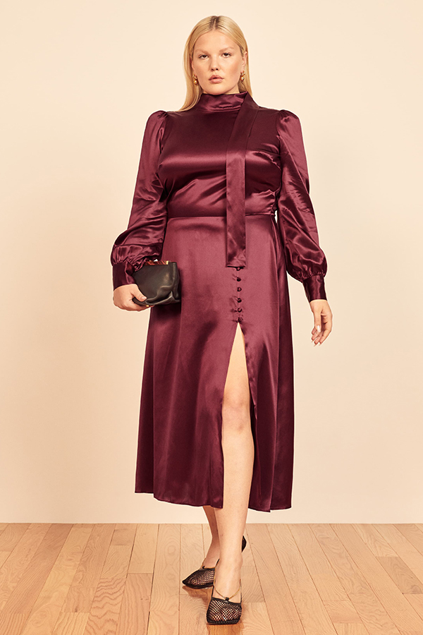 A plus-size model wearing a burgundy satin midi dress.