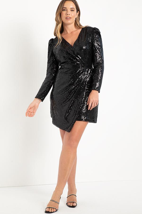 A plus-size model wearing a black sequin wrap dress.