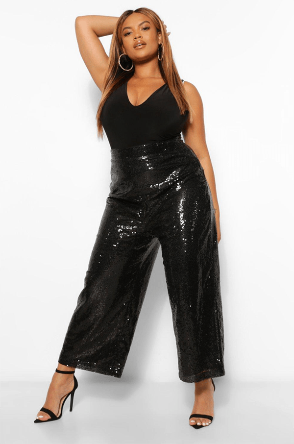 A plus-size model wearing a pair of wide-leg black sequin pants.
