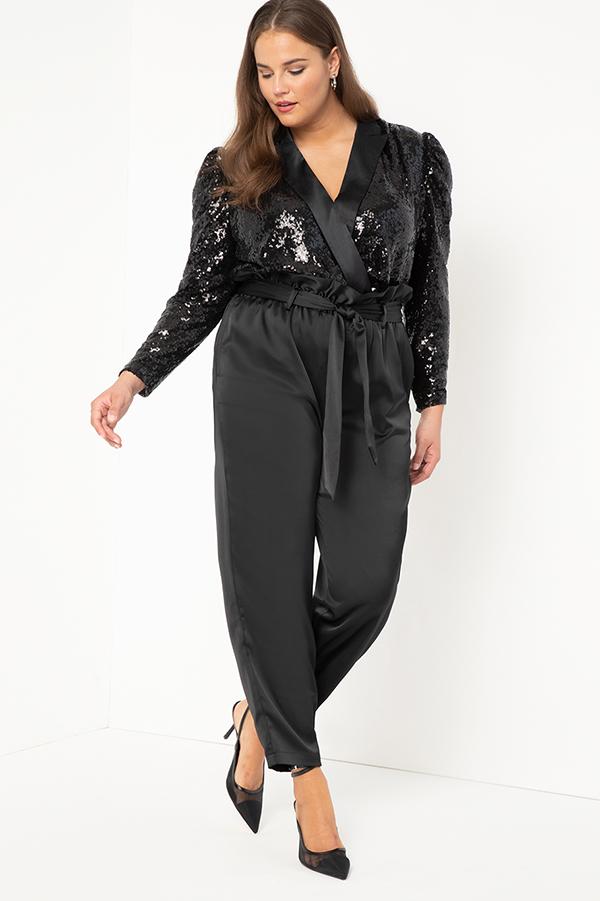 A plus-size model wearing a black sequin bodysuit.