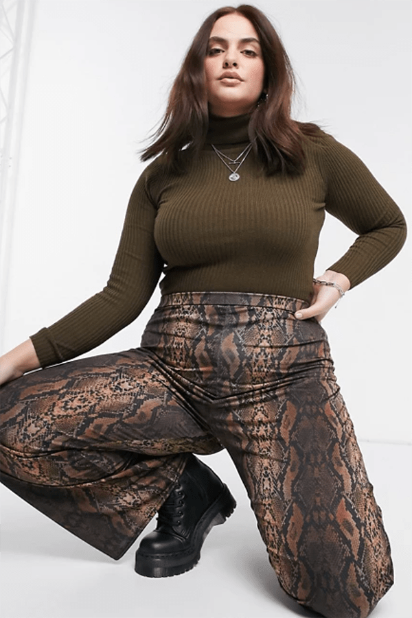 A plus-size model wearing snake print flare pants.
