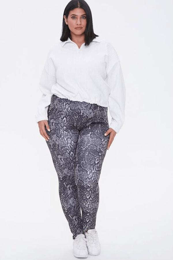 A plus-size model wearing gray snake print leggings.