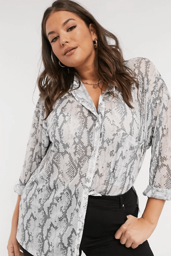A plus-size model wearing a snake print button-up shirt.