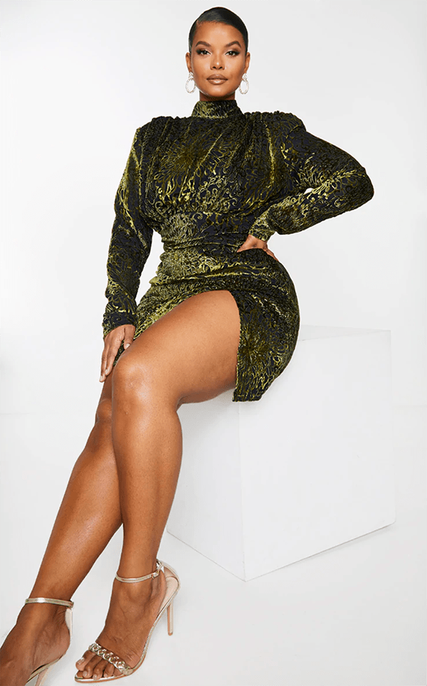 A plus-size model wearing an olive green velvet dress.