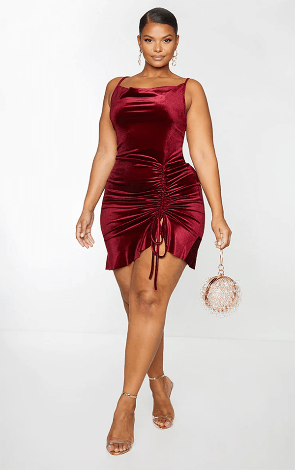 A plus-size model wearing a burgundy velvet ruched mini dress.