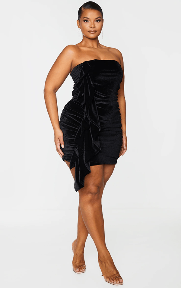 A plus-size model wearing a black velvet strapless mini dress.