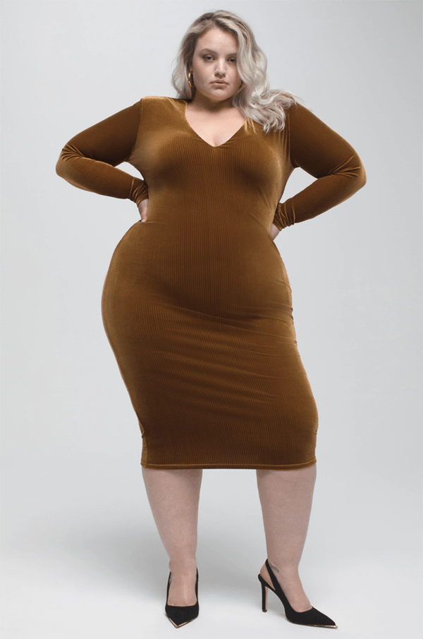 A plus-size model wearing a brown velvet bodycon midi dress.