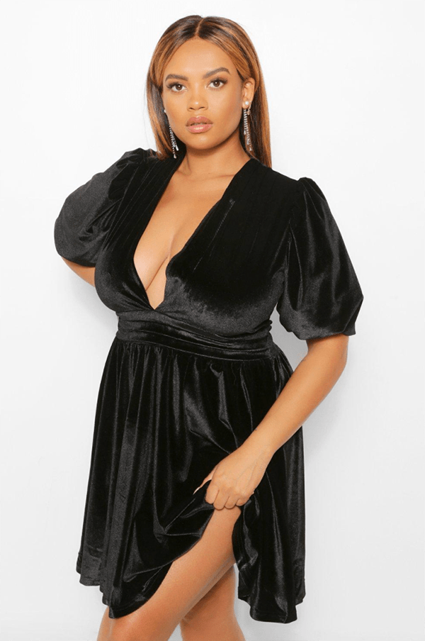 A plus-size model wearing a black velvet dress.