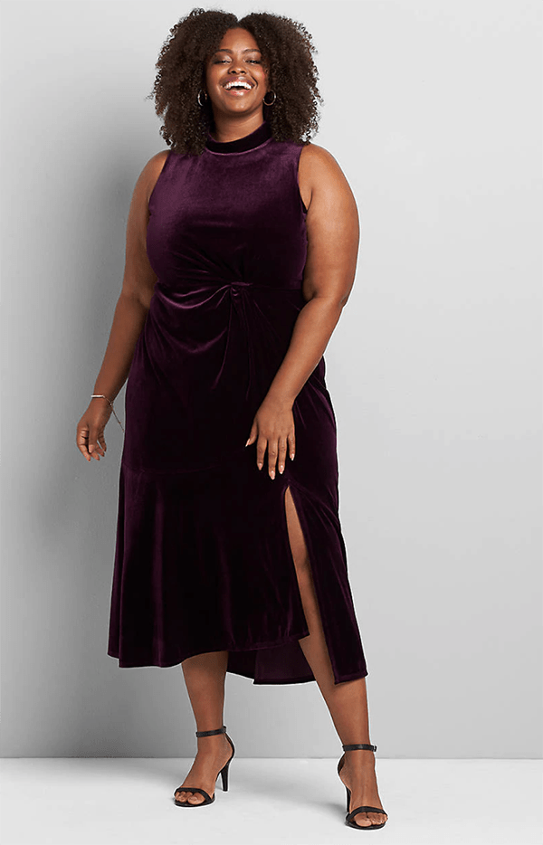 A plus-size model wearing a maroon velvet midi dress.
