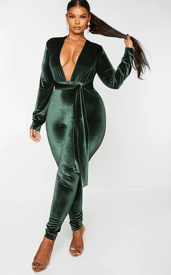 A plus-size model wearing a green velvet jumpsuit.
