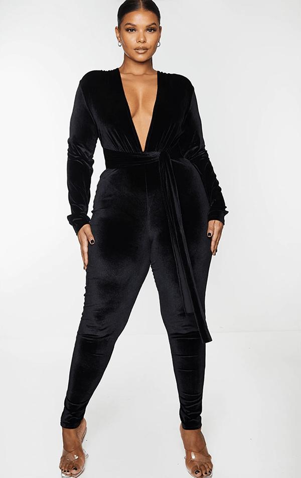A plus-size model wearing a black velvet jumpsuit.