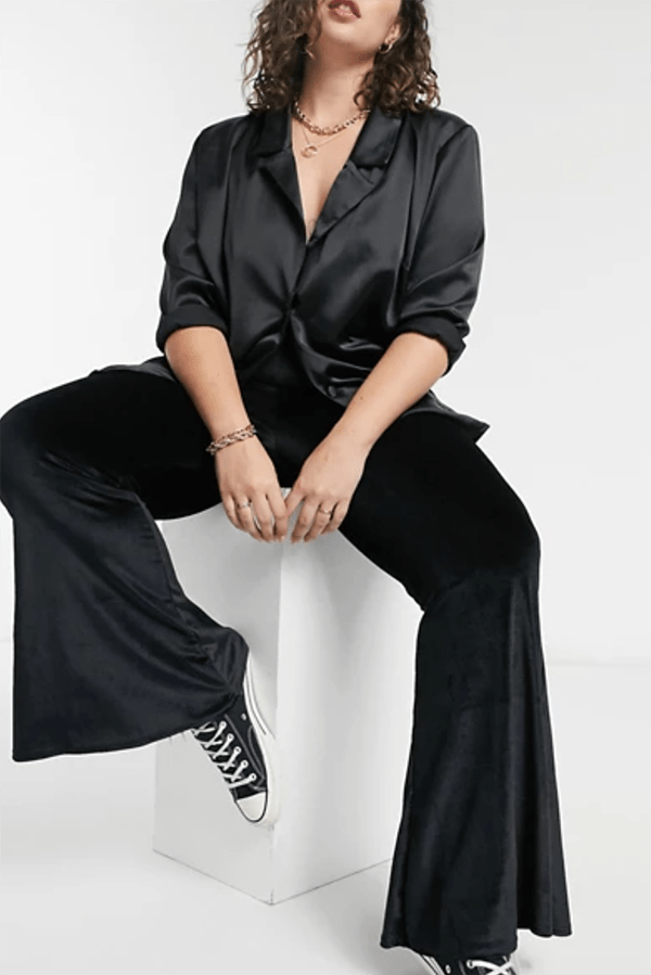 A plus-size model wearing black velvet flare pants.