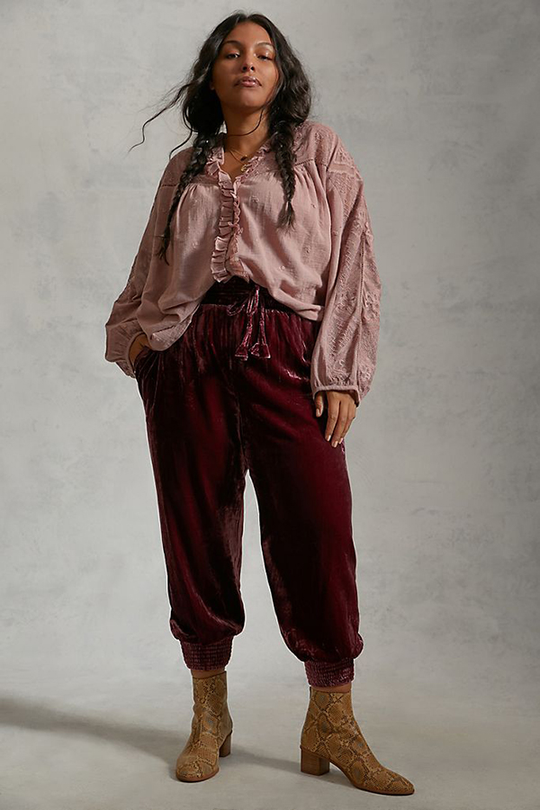 A plus-size model wearing burgundy velvet joggers.