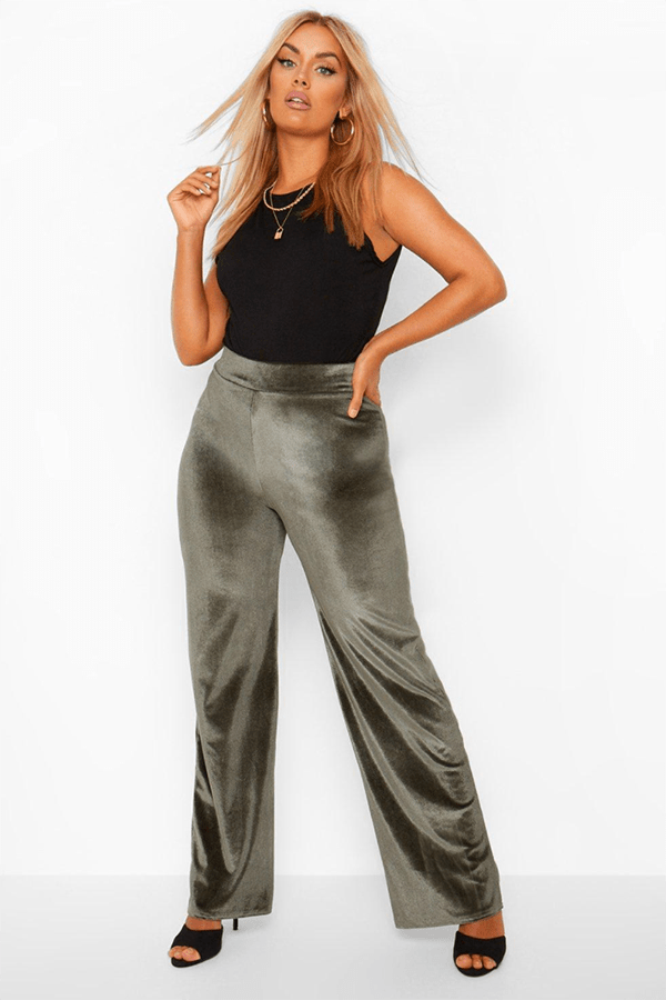 A plus-size model wearing olive green wide-leg velvet pants.