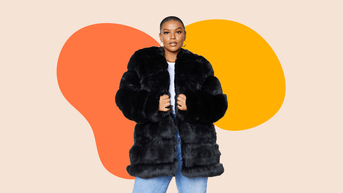 A plus-size model wearing a faux fur black coat.