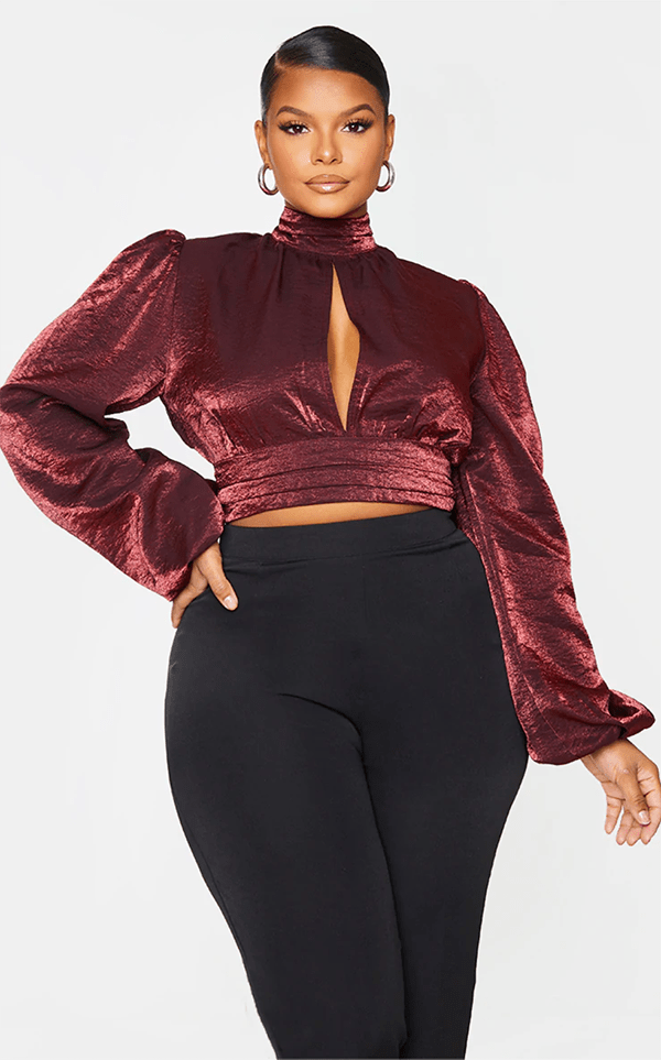 A plus-size model wearing a burgundy satin crop top, which will be marked down at PrettyLittleThing's Black Friday 2020 sale.
