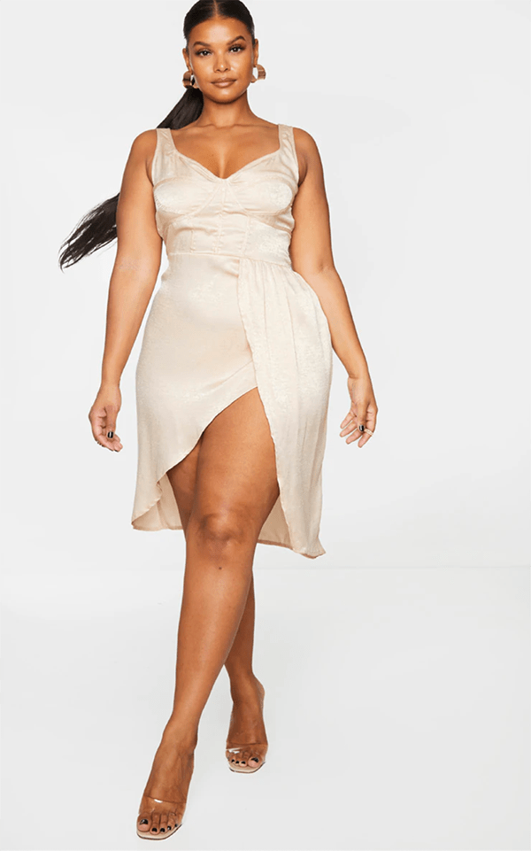 A plus-size model wearing an off-white satin dress, which will be marked down at PrettyLittleThing's Black Friday 2020 sale.
