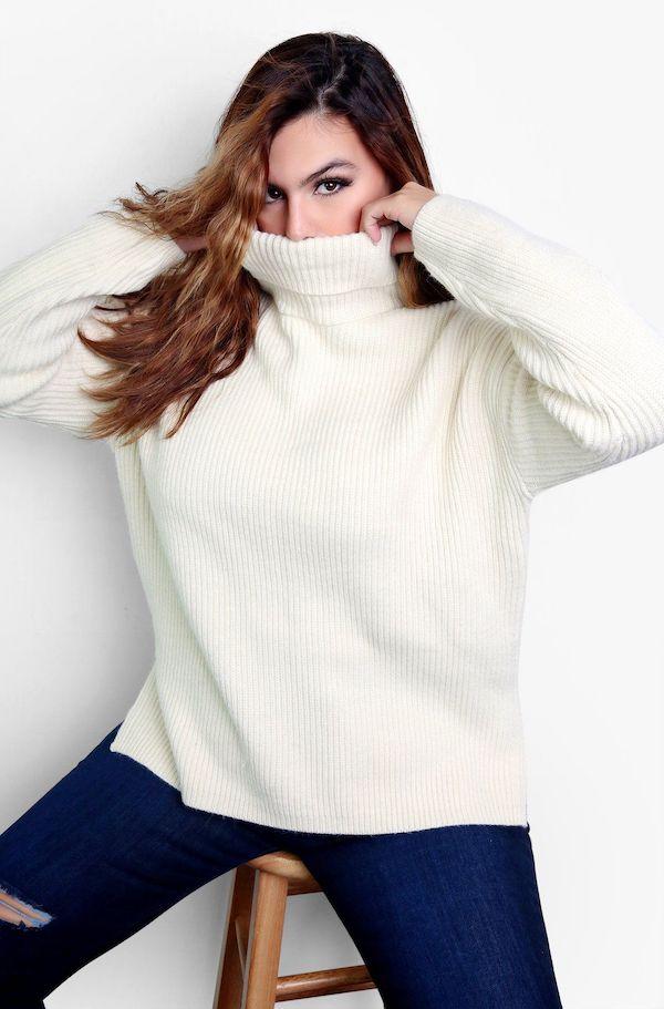 A model from Rebdolls wearing a cream turtleneck sweater.