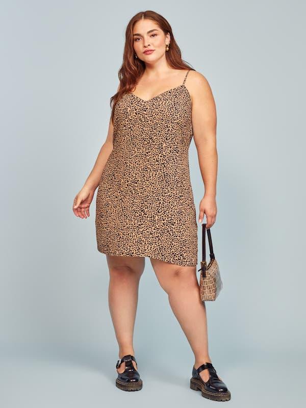 A plus-size model from Reformation wearing a mini leopard print mini dress.