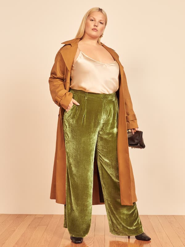 A plus-size model from Reformation wearing green velvet trousers.