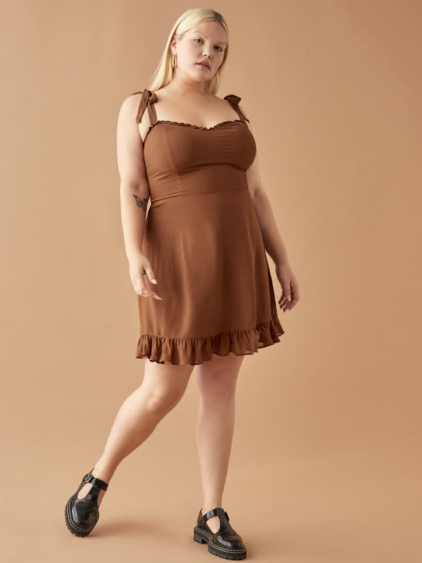 A plus-size model from Reformation wearing a brown mini dress.