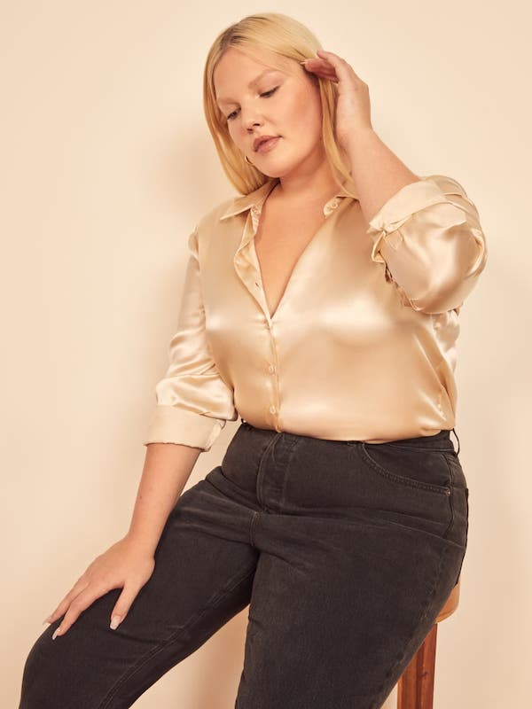 A plus-size model from Reformation wearing a gold blouse.