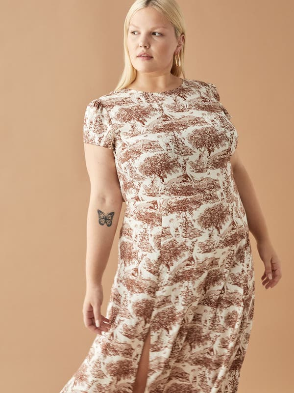 A plus-size model from Reformation wearing a patterned white and brown dress.
