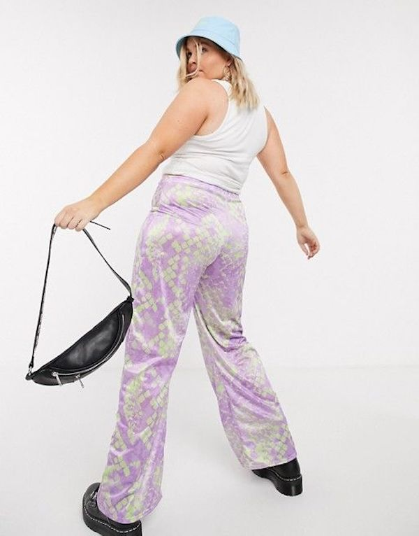 A plus-size model wearing a pair of purple snake print pants.
