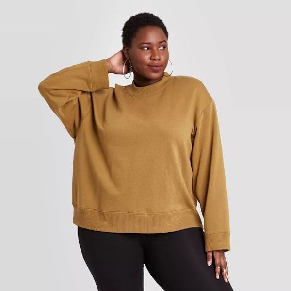 A plus-size model from Target wearing a light brown sweater.