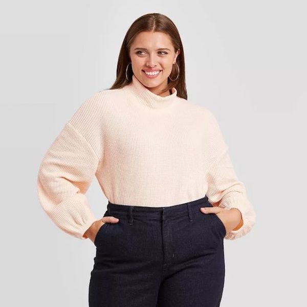 A plus-size model from Target wearing a pale pink turtleneck.