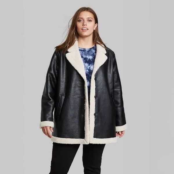 A plus-size model from Target wearing a leather and sherpa jacket.