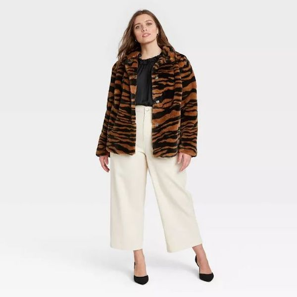 A plus-size model from Target wearing a fuzzy animal print jacket.