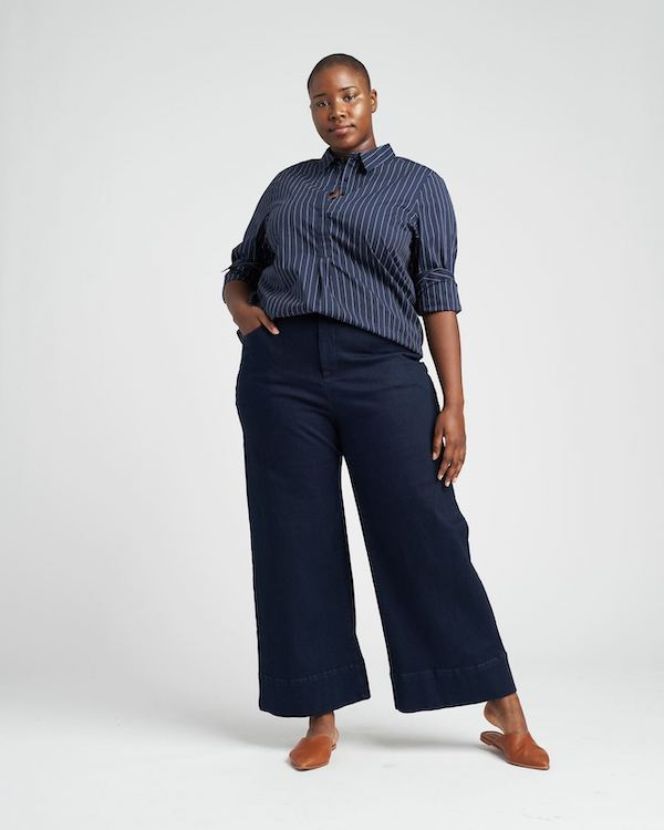 A plus-size model from Universal Standard wearing jeans and a striped top.