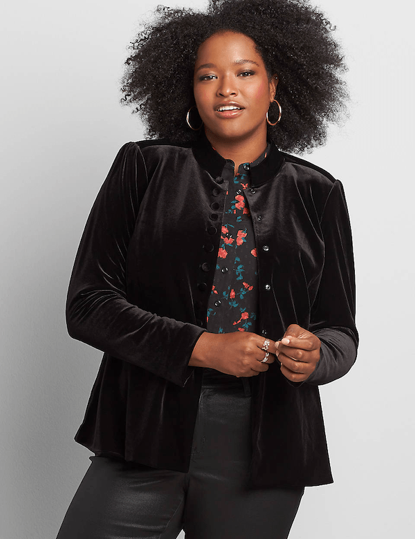 A plus-size model wearing a black velvet jacket.