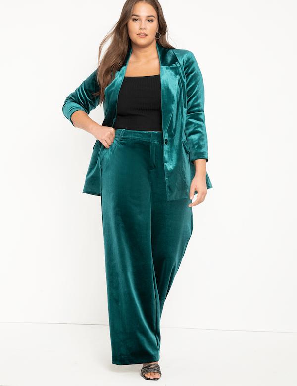 A plus-size model wearing a green velvet jacket.
