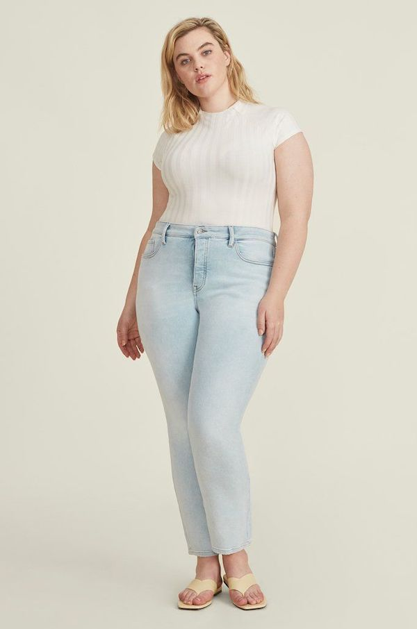 A plus-size model from Warp + Weft wearing light-wash skinny jeans.