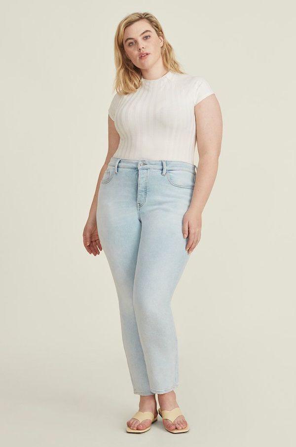 A plus-size model from Warp + Weft wearing light-wash skinny jeans.