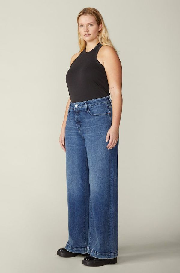 A plus-size model from Warp + Weft wearing mid-wash wide-leg straight jeans.