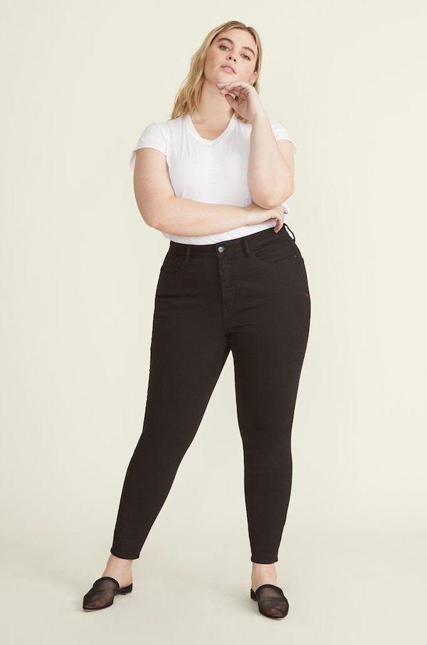 A plus-size model from Warp + Weft wearing black skinny jeans.