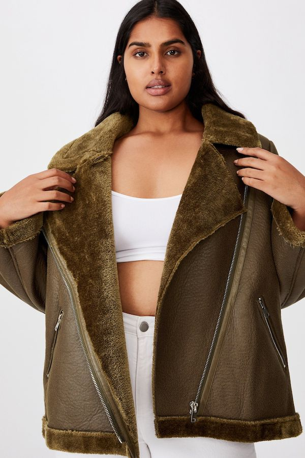 A model wearing a plus-size aviator jacket in dark olive green.