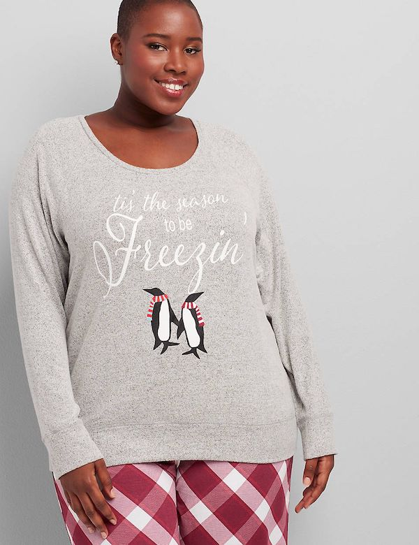 A model wearing a plus-size gray sleep shirt with penguins.