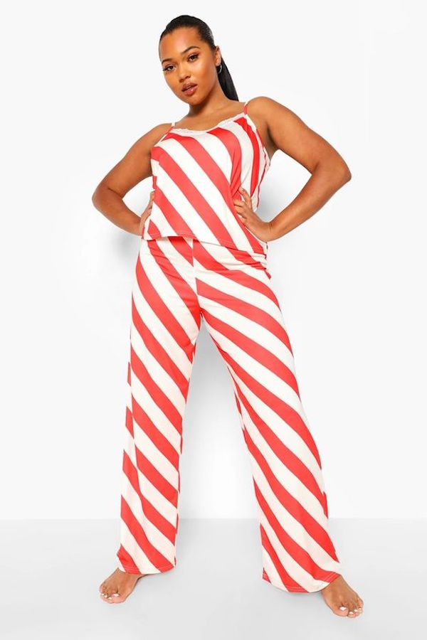 A model wearing plus-size red and white stripe Christmas pajamas.
