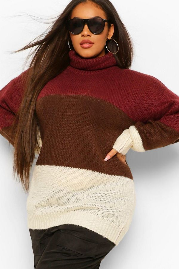 A model wearing a plus-size colorblock sweater in red, burgundy, and cream.