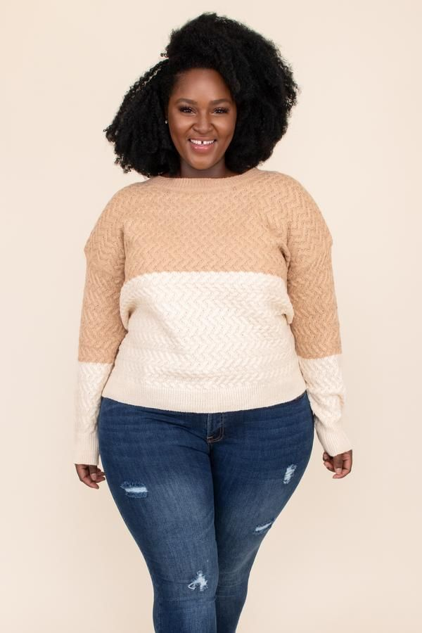 A model wearing a plus-size colorblock sweater in tan and cream.
