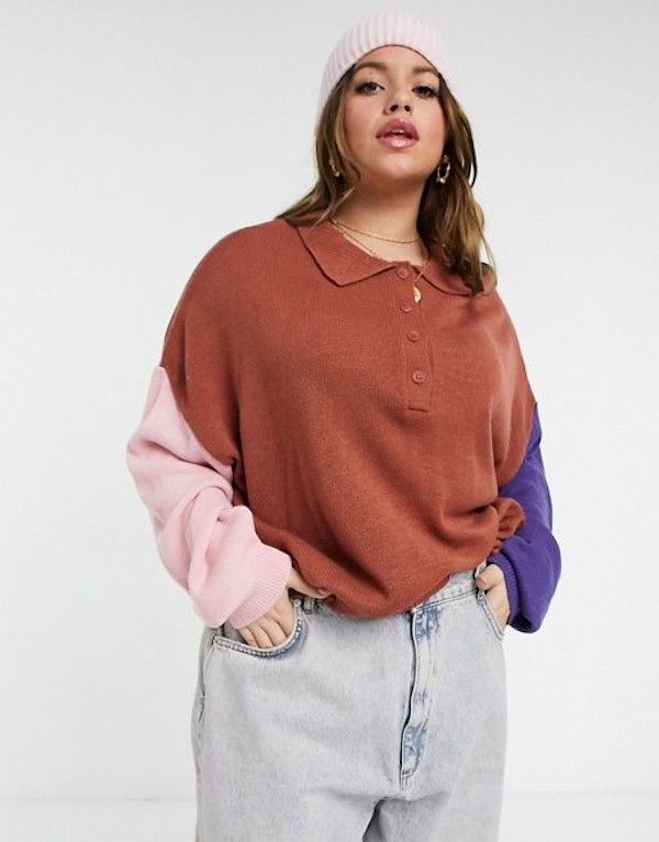 A model wearing a plus-size colorblock sweater in burnt red, pink, and blue.