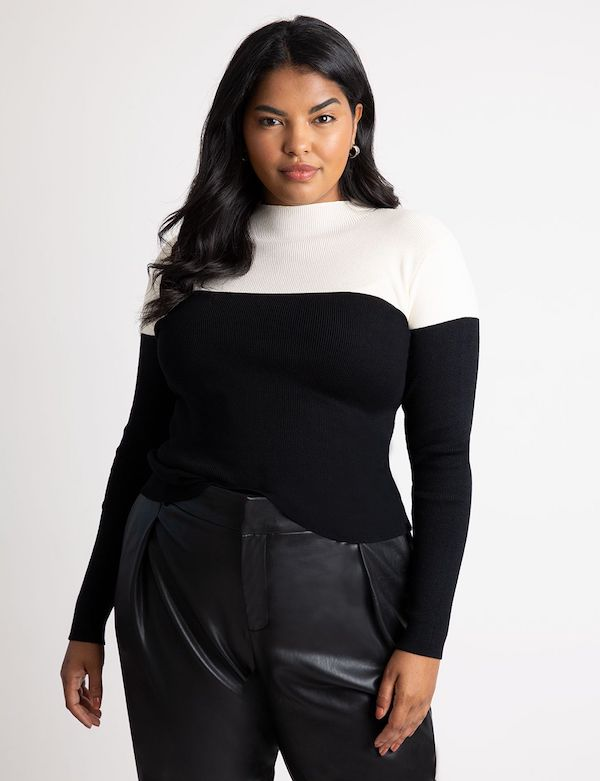 A model wearing a plus-size colorblock sweater in black and white.