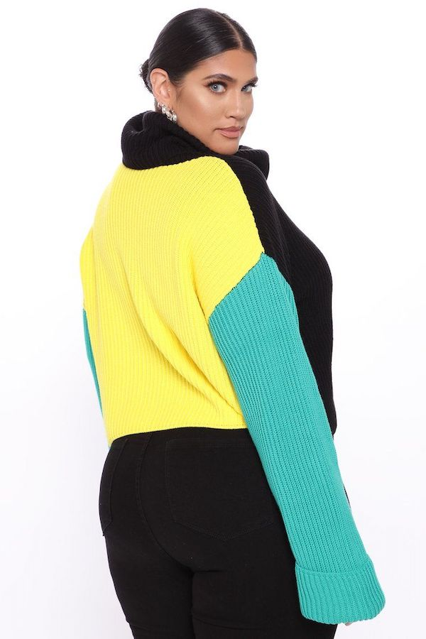 A model wearing a plus-size colorblock sweater in black, yellow, and green.
